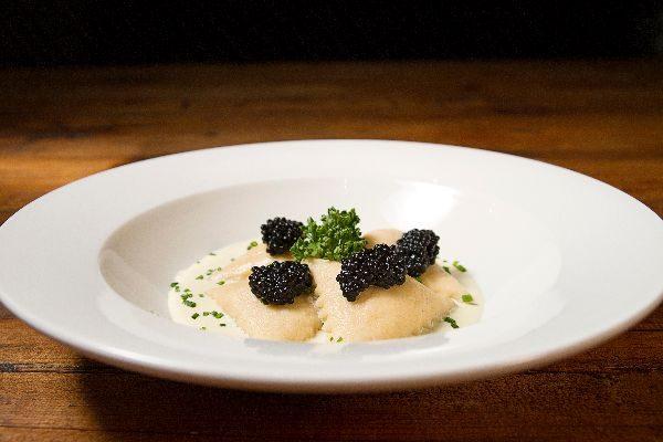 Ravioli relleno de crema de salmón Chovas sobre lecho de sopa de vieira y perlas de arenque de Pescaviar